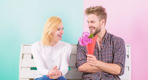 Pleasant surprise for lady. Flowers for her. Man gives bouquet flowers to girlfriend. He guessed her favorite flower. Man women sit bench romantic date stock photo