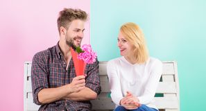 Pleasant surprise for lady. Flowers for her. Man gives bouquet flowers to girlfriend. He guessed her favorite flower. Man woman sit bench romantic date stock image
