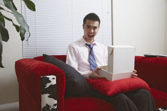 A pleasant surprise in a package. A young Asian man opens a package that makes him really happy Stock Image