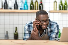 Cheerful young waiter talking on the phone while being at work. Pleasant talk. Positive young friendly waiter looking happy while being at work and talking on Stock Photo
