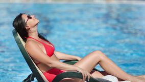 Pleasant tanned travel woman in red bikini relaxing on deck chair near swimming pool at hotel