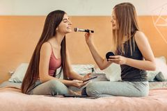 Pleasant teenage girls training in applying makeup. Let me help. Pretty teenage girl sitting on the bed together with her best friend and applying some makeup to Royalty Free Stock Photography