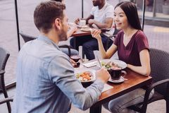 Pleasant tender couple resting at cafe. Lovely atmosphere. Top view of sincere young happy couple posing at cafe and women eating salad while grinning stock image