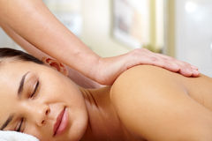 Pleasant therapy. Portrait of young and calm female enjoying body massage royalty free stock photos