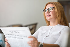 Pleasant thoughtful woman reading newspaper Royalty Free Stock Photography