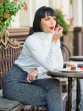 Pleasant time and relaxation. Delicious gourmet cake. Woman attractive brunette eat gourmet cake cafe terrace background royalty free stock photography