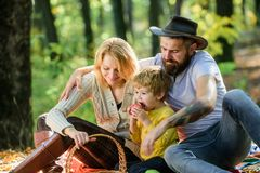Pleasant time spending. Family picnic. Mother, cowboy father love their little boy child. Spring mood. Happy family day. Sunny weather. Healthy food. Happy son royalty free stock photo