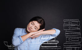 Pleasant tired woman sleeping on the books Royalty Free Stock Image