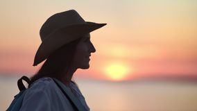 Pleasant tourist hipster female in hat enjoying freedom admiring beautiful sunset over sea side view. Independent smiling active hiker woman relaxing in dusk stock video footage