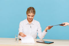 Pleasant TV announcer giving folder Royalty Free Stock Photography