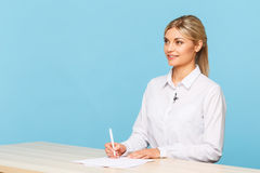 Pleasant TV announcer sitting at the table Stock Photography