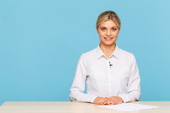 Pleasant TV announcer sitting at the table Royalty Free Stock Image