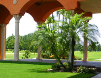 Pleasant View. Of terra cotta arches and white columns, tropical setting, with palms and old oak trees, Mediterranean architecture, overlooking green lawn royalty free stock images