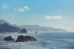 Pleasant view of rocks bounding by water. Breathtaking show of stream washing big stones in Oregon state Cannon beach stock photography
