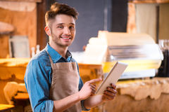 Pleasant waiter working in the cafe. Like what you do. Cheerful handsome young smiling waiter using tablet and expressing gladness while working in the cafe royalty free stock photo