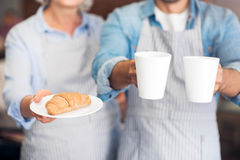 Pleasant waiters holding croissants and tea Stock Images