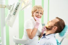 Pleasant woman dentist took off her mask, looks into camera royalty free stock image