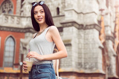 Pleasant woman drinking coffee. Refresh your mind. Pleasant delighted charming woman holding coffee and resting while having a walk Stock Photos