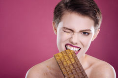 Pleasant woman eating chocolate bar. Abate your hunger. Pleasant delighted woman holdign chocolate bar and biting it while looking at you Royalty Free Stock Image