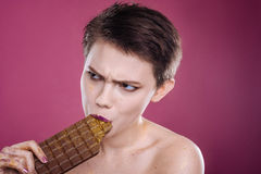 Pleasant woman eating chocolate bar. It is mine. Pleasant involved woman holding chocolat bar and eating it while standignagainst pink background Stock Photography