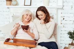 Pleasant woman enjoying talk with her caring charming granddaughter Stock Images