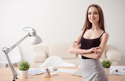 Pleasant woman expressing confidence. Confidence in mind. Positive beautiful woman folding her hands and smiling while working in the office Royalty Free Stock Photo