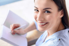 Pleasant woman expressing positivity. Life is great. Portrait of nice beautiful woman smiling and holding notebook while making notes stock image
