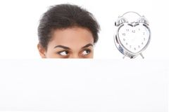 Pleasant woman fixedly looking at alarm clock Stock Images