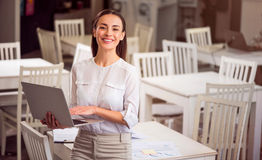 Pleasant woman holding laptop. Express your emotions. Cheerful content smiling woman standing near table and expressing joy while holding laptop stock photos