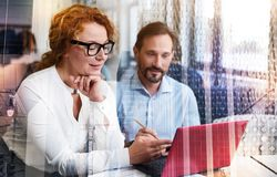 Pleasant woman making remarks on project presentation. Crucial remarks. Charming red-haired women sitting next to her male colleague and making some remarks Royalty Free Stock Images