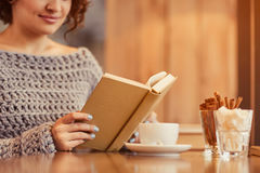 Pleasant woman reading book in the cafe Royalty Free Stock Photography