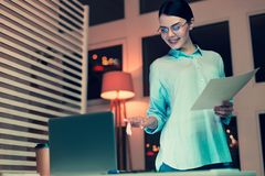 Pleasant woman reading a printout and pointing at laptop. Checking information. Pleasant young woman in eyeglasses pointing at the laptop screen while analyzing royalty free stock images