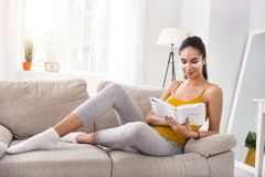 Pleasant woman reading psychology book on sofa. Interesting book. Charming young woman lying on the sofa and reading a psychology book while wearing under-eye Royalty Free Stock Photo