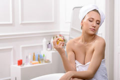 Pleasant woman sitting in the bathroom. Divine aroma. Delighted pleased young woman holding bottle with perfume and enjoying the scent with closed eyes while royalty free stock images