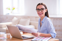 Pleasant woman sitting at the table. Charged with emotions. Cheerful pleasant smiling beautiful woman sitting at the table and expressing gladness while working royalty free stock photography