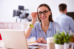 Pleasant woman sitting at the table. Full of gladness. Pleasant charming delighted women sitting at the table and smiling while being involved in work stock images