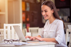 Pleasant woman sitting at the table. Like my work. Cheerful delighted beautiful smiling woman sitting at the table and working on the laptop while expressing royalty free stock image