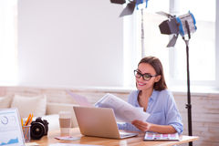 Pleasant woman sitting at the table. Pleasant work. Cheerful charming smiling woman sitting at the table and working with papers while expressing gladness royalty free stock images