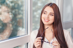 Pleasant woman standing near window Stock Photo