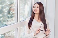 Pleasant woman standing near window Royalty Free Stock Image