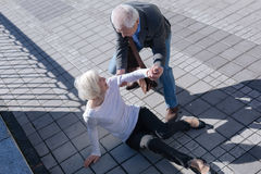 Pleasant woman tumbling over outdoors. Do not afraid of falling down. Funny white-haired slim lady catching foot and receipting of relief from aged men who Stock Images
