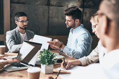 Pleasant working day. Group of young modern people in smart casual wear discussing business while sitting in the creative office stock image