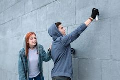Pleasant young couple drawing graffiti on the wall royalty free stock images