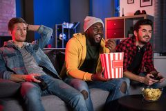 Pleasant young guys are enjoying time together. Joyful mood. Cheerful relaxed men with joystick and popcorn are resting at home while playing video game. They stock photo