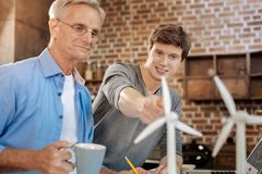 Pleasant Young Man Pointing At Wind Turbines To His Mentor Royalty Free Stock Photo