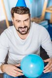 Pleasant young man posing with a blue balloon Royalty Free Stock Photo
