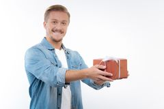 Pleasant young man posing with a gift box. Gift with love. Pleasant young man posing on a white background while holding a gift box in his outstretched hands as Royalty Free Stock Image