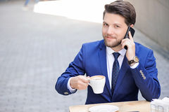 Pleasant young man sitting in cafe Stock Images