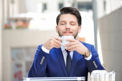 Pleasant young man sitting in cafe Royalty Free Stock Photos