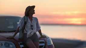 Pleasant young travel woman relaxing waving hair sitting on car bonnet enjoying dusk sunset seascape. Medium shot. Backpacker tourist female having evening stock footage